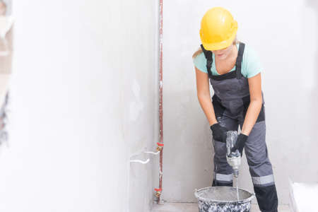 Woman builder worker kneads cement and plaster with mixer to level gray concrete walls