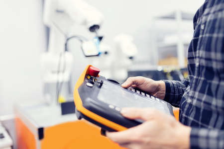 Operator uses radio remote to control robot arm with automatic hand