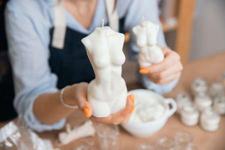 Scented curly candles in form of Goddess venus large female body in woman master hand 版權商用圖片