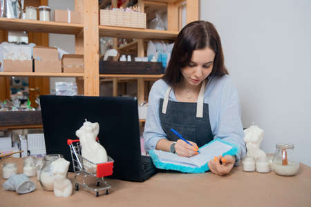 Young woman artisan works with laptop workplace, surrounded by wax candles of DIY own production