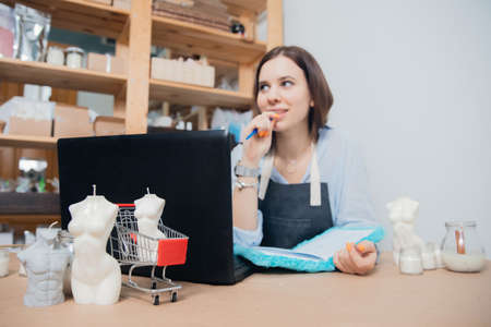 Woman business owner counting revenue, selling DIY production aroma wax candles in form female body on online web platform