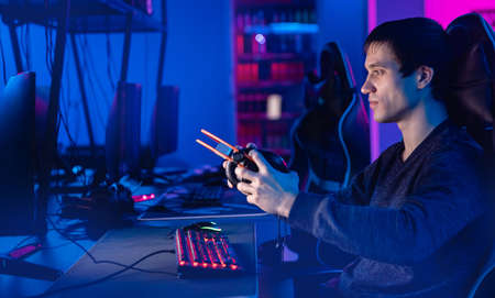 Streamer professional cyber sport gamer playing online computer game with headphones, Blurred Red and Blue background 版權商用圖片