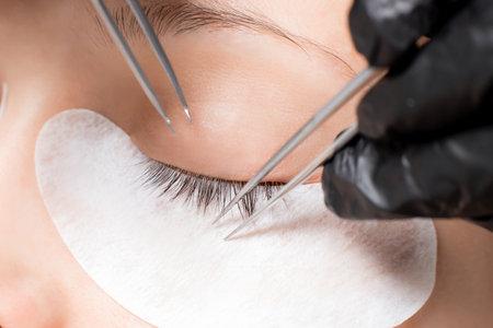 Master tweezers fake long lashes beautiful female eyes. Eyelash extension procedure