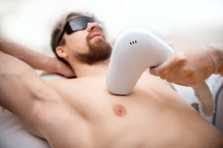 Man torso under treatment in hair removal laser epilation studio 版權商用圖片