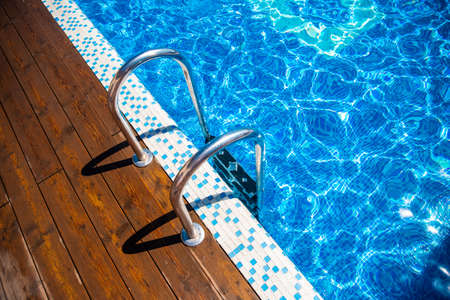 Grab wooden ladder in blue water swimming pool, sunlight Reklamní fotografie