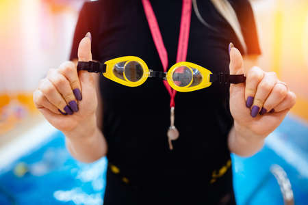Close-up goggles for swimming in hands of trainer woman coach. Swim school for people