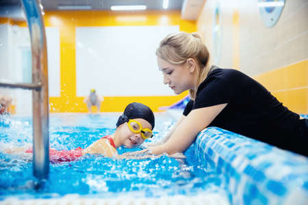 Child girl swimmer in red bathing suit on background of pool with glasses. Concept training sport swimming 版權商用圖片