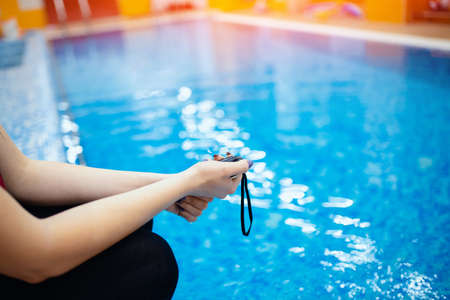 Swimming instructor coach people, woman hold in hand stopwatch during competitions in pool