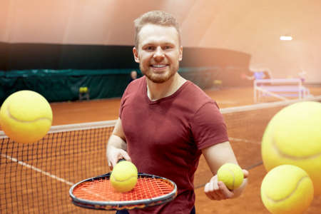 Happy trainer tennis player man smiling with racket and ball on court