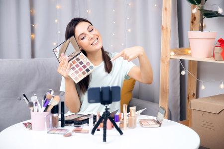 Happy woman beauty blogger recording makeup tutorial video stream on phone. Concept Influencer blog cosmetics 版權商用圖片