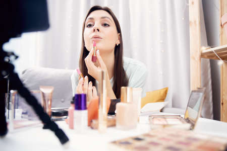 Happy woman vlogger is showing cosmetics products while recording video stream on phone. Concept Influencer blogger beauty blog 版權商用圖片