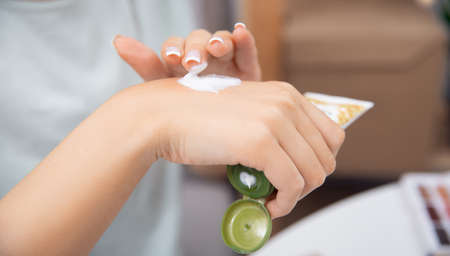 Concept winter cold season hands skin care protection. Woman applying protective cream