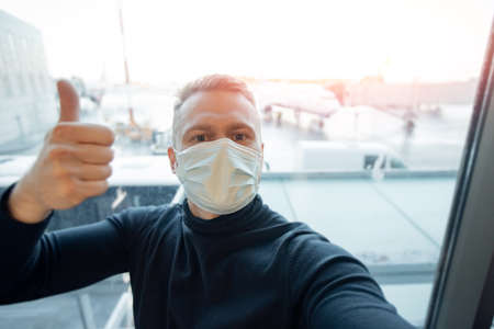 Portrait of tourist man in safe medical mask in airplane, concept travel trip in covid