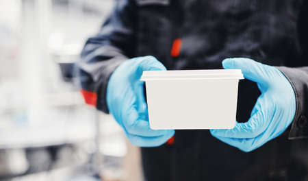 Factory engineer holds finished product in white box with place for logo, copy space.