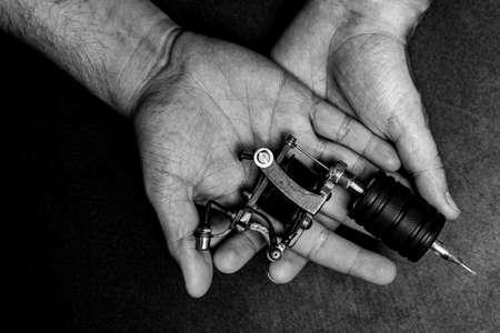 Man artist holding tattoo machine on hand, top view black and white color