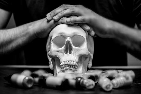 Tattoo artist folded hands on plaster skull surrounded by typewriter ink, black and white photo