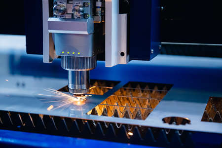 CNC Laser engraving cutting of heavy metal with light spark. Concept background modern industrial technology