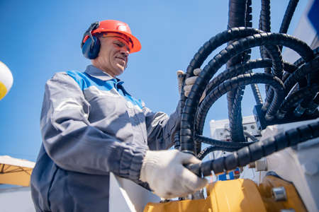 Industrial worker fuel electrician factory in hard hat and headphones monitors electric cable at oil well