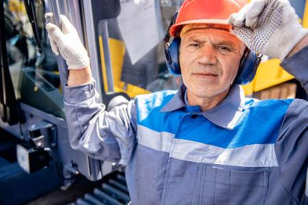 Portrait smile Industrial worker engineer old man in protective helmet and headphones background factory 版權商用圖片