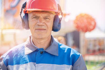 Industrial miner worker man in protective helmet and headphones in uniform on background of factory mine coal, sunlight background 版權商用圖片
