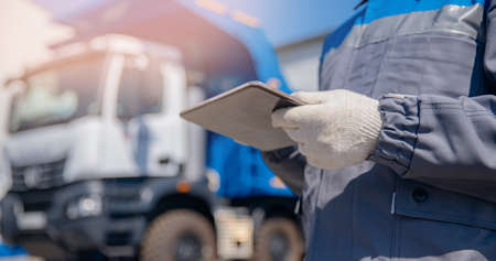 Concept banner automated logistics online internet. Dump truck driver man in uniform with tablet computer controls loading of cargo or coal 版權商用圖片