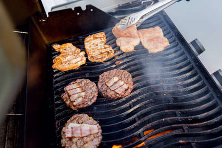 Cook grills burger patties and pork ribs open fire. Turns meat over with tongs 版權商用圖片