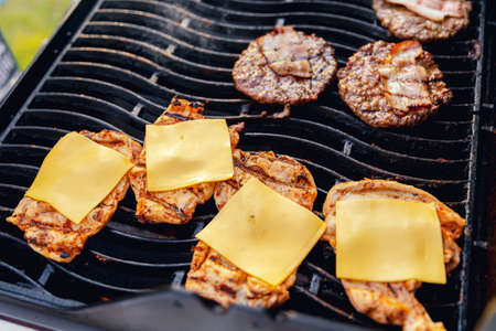 Cook grills burger patties and cheese pork ribs open fire. Turns meat over with tongs 版權商用圖片