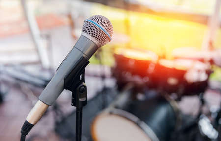 Electronic microphone on background of musical instruments drums with glare of sun, concept of summer vacation concert