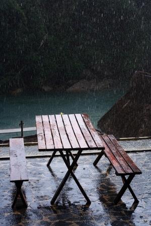 Wooden Bench Beside River Among Falling Rain