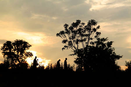 Silhouette of three men walking in the evening sky Among the Forest