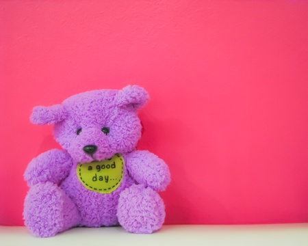 purple teddy bear sitting in front of pink wall Stock Photo