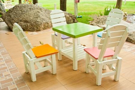 muebles de madera: cuatro sillas de colores y una mesa