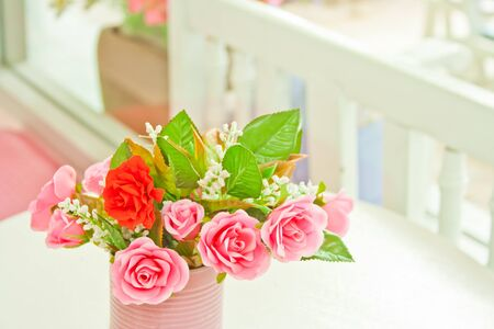 pink artificial roses setting on white table