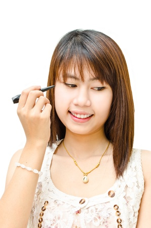 young cute girl using eye liner with her eye  photo