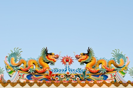 twin dragon on the roof of shrine with blue sky background