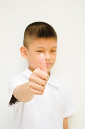 angry asian boy show his thumb to someone on white background Stock Photo - 11289246