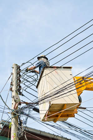 electrician repairing electric wire at electricity post