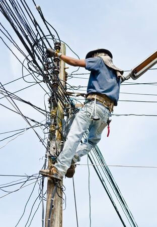 worker climbing electricity post for repairing Stock Photo