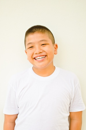 young asian boy smiling on white background
