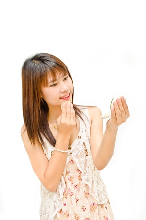 young asian girl make up her face on white background photo
