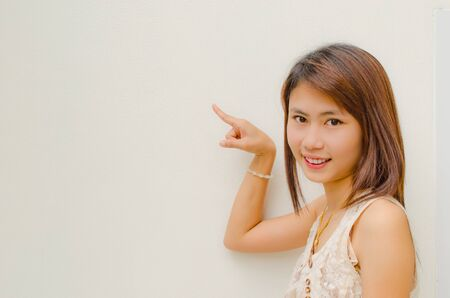 asian cute girl smile and point on white background
