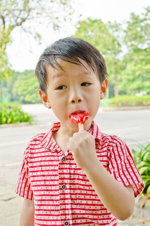 young asian boy eating fruit flavour ice-cream in park photo