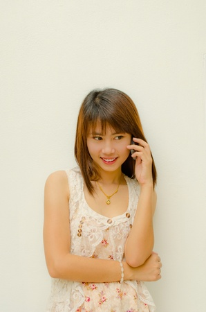 young asian girl chatting with her friend by mobile phone photo