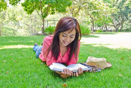 Thai woman lie on ground and reading book in park Stock Photo