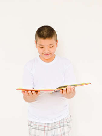 Asian boy reading book on white background