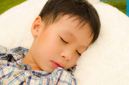 asain boy sleeping in the garden
