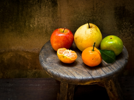 Fresh orange and pear on an old wood table,still life