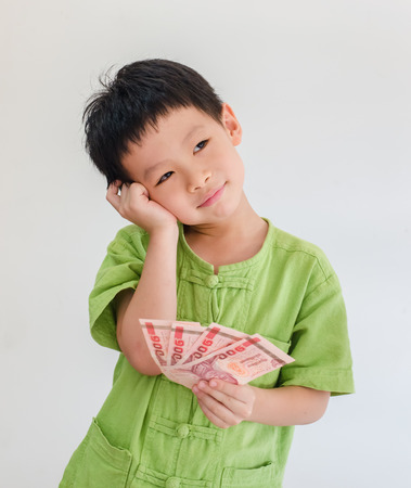 Asian boy thinking with holding Thai money on hand over white background