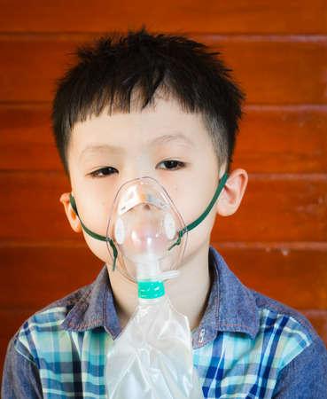 Asian boy wearing oxygen mask photo