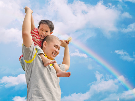 Happy father and son with sky and rainbow background photo